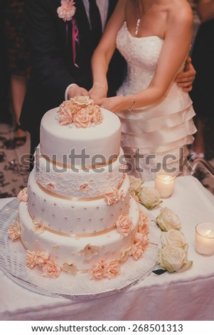 A bride and a groom is cutting their wedding cake. - stock photo