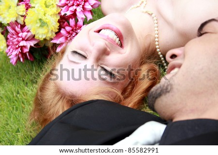 A bride and a groom lying on the grass, smiling - stock photo