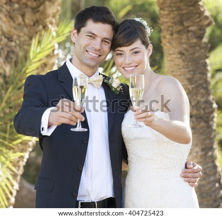 A bride and groom drinking champagne - stock photo