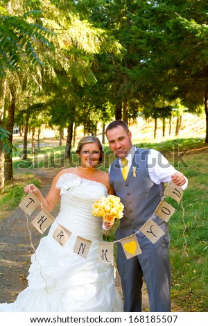 A bride and groom hold a banner of burlap that reads thank you so they can use it later for their thank you cards. - stock photo