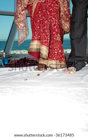 A bride and groom perform a series of steps as part of a traditional Hindu wedding ceremony - stock photo