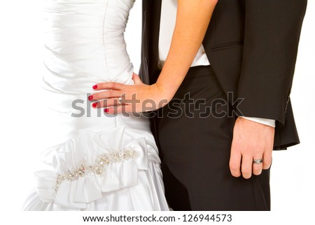 A bride and groom portrait showing only their bodies and their hands against a white background. You can see the wedding rings on the fingers. - stock photo