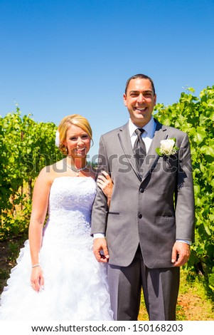 A bride and groom pose for portraits on their wedding day at a winery vineyard outdoors in oregon. - stock photo