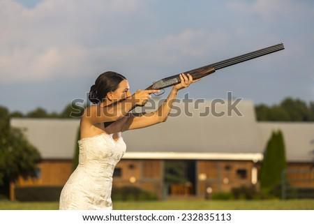A bride in a wedding dress shooting a shotgun - stock photo