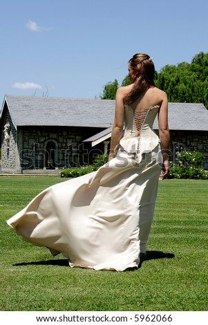 A bride walking outside and wind blowing her dress - stock photo