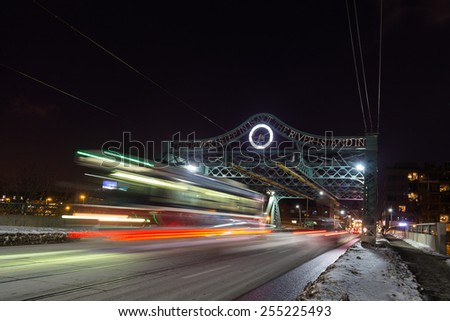 A bridge in East Toronto with the blur of a Streetcar at night - stock photo