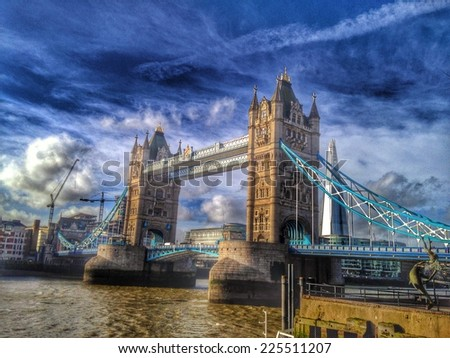 A bridge over a body of water on a cloudy day. - stock photo
