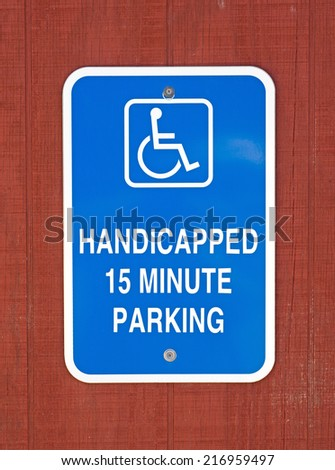 A bright blue handicapped parking sign with a fifteen minute time limit attached to stained plywood siding. - stock photo