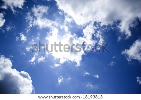 A bright blue sky and perfect cottony clouds with the sun trying to shine through - stock photo