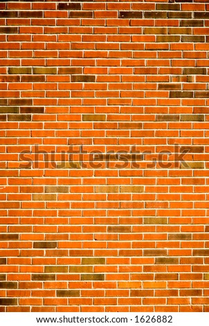 A bright brick wall lit by the late day sun. - stock photo