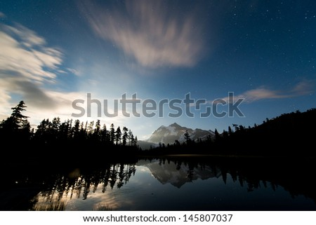 A bright moon is  rising up at night. Picture Lake and Mt Baker. - stock photo