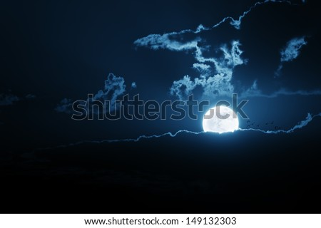 A bright moon rises over a breaking cloud bank. A flock of birds seems to be flying directly at the moon.  All my own components to create illustration. - stock photo
