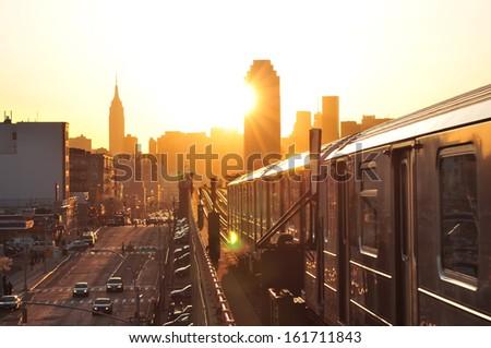 A bright orange sunset illuminates a large city. - stock photo