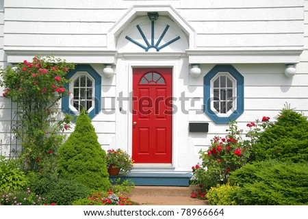 A bright red door on the entrance of a home. - stock photo