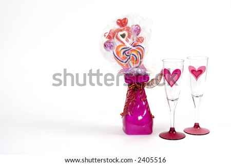 A bright red vase with valentine candy and two wine glasses isolated on white with room for text. - stock photo