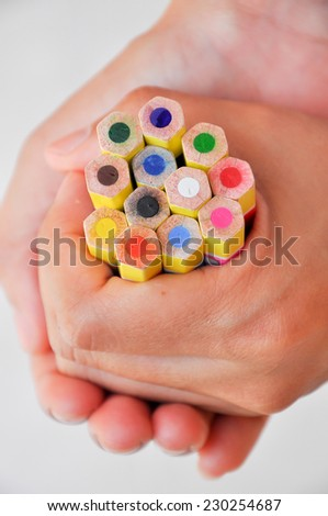 A brightly colored pencils in her handful. - stock photo