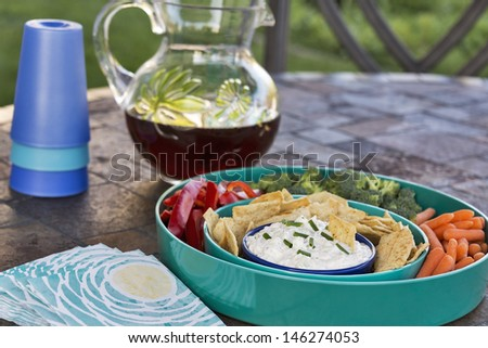 A brightly colored tray full of dip, pita chips and fresh vegetables is served outdoors with a pitcher of iced tea. - stock photo