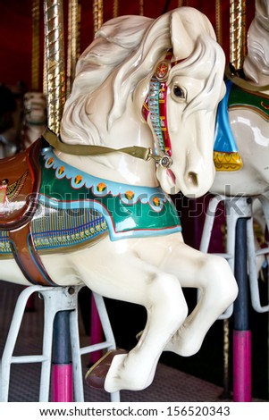 A brightly painted white carousel horse waits for a rider. - stock photo