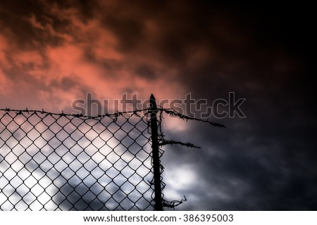 A broken fence over the sunset sky. Barbed wire on top. Symbolic shot: escapism, jail, hope, war.  - stock photo