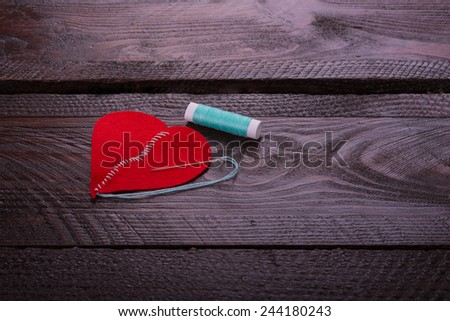 a broken heart and a thread on a wooden background - stock photo