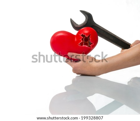 A broken heart in his hand and wrench - stock photo