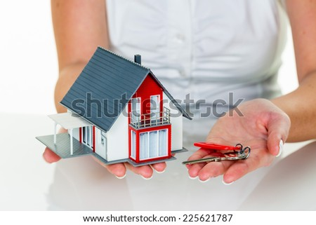a broker for real estate with a house and a key. successful leasing and home sales by real estate agents. - stock photo