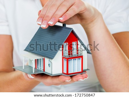a broker for real estate with a house and a key. successful leasing and property for sale by real estate agents. - stock photo