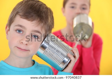 A brother and a sister talking through cans and a rope. - stock photo