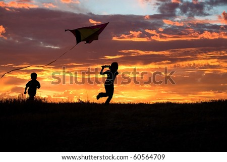 A brother and sister getting a kite to fly suring sunset. - stock photo