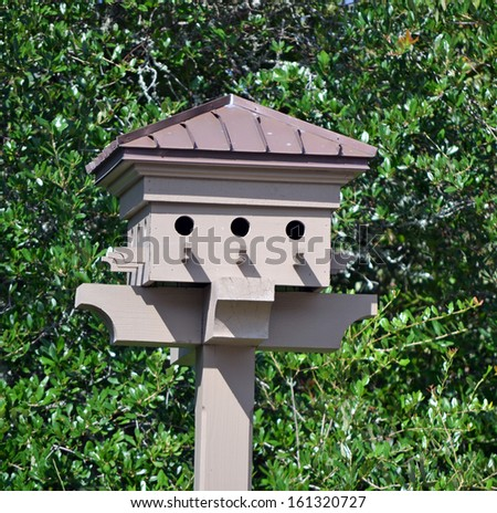 A brown birdhouse on a wooden post - stock photo