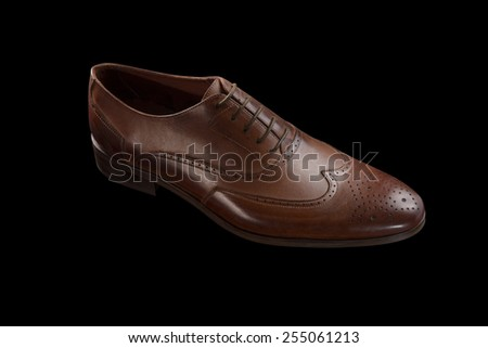 A Brown Classic Male Shoe on Solid Black Background - stock photo