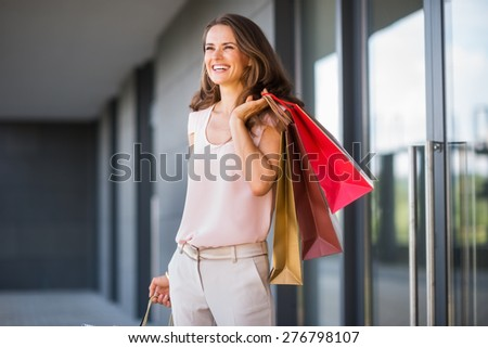 A brown-haired woman holding three shopping bags - gold, brown, and red - over her left shoulder laughs and smiles as she looks out into the distance. She is relaxed, and effortlessly stylish. - stock photo