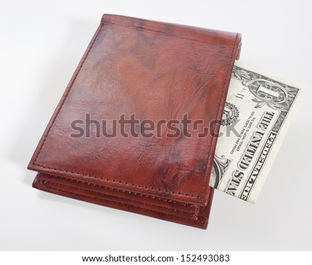 a brown leather wallet with a one dollar bill inside, focus on front of wallet - stock photo