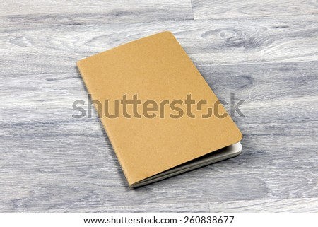 a brown paper notebook on a wood floor - stock photo
