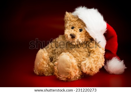 A brown teddy bear wearing a Christmas hat sitting isolated against a black and red background - stock photo