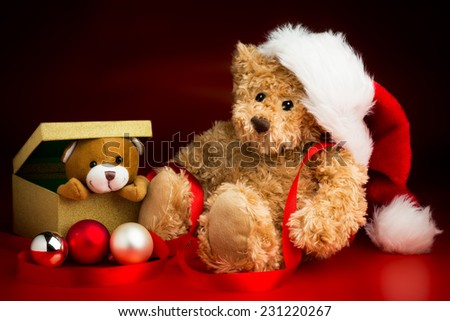 A brown teddy bear wearing a Christmas hat sitting next to a box with a teddy bear peeking out over the edge isolated against a red and black background and three baubles in front of them. - stock photo