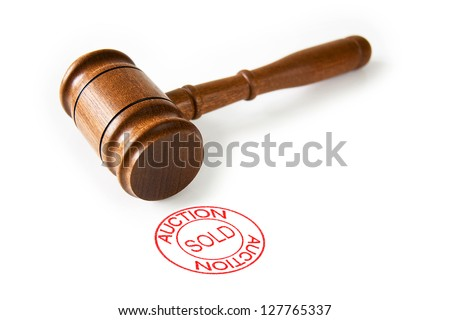 A brown wooden auctioneer's hammer with a red circle sold stamp - stock photo