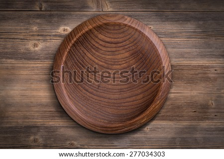 A brown wooden bowl on wooden surface - stock photo