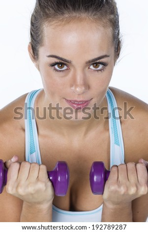 A brunette fitness model works out with small weights - stock photo
