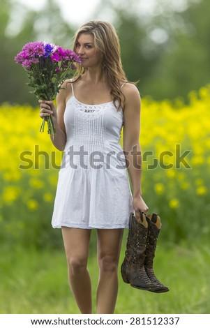 A brunette model walking on a road near a field of flowers - stock photo