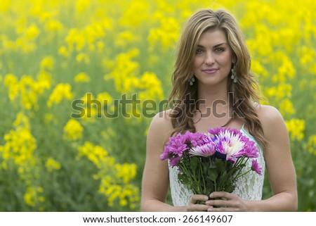 A brunette model walks in a field of flowers - stock photo