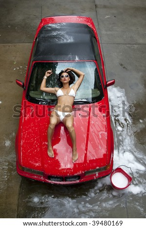 A brunette model washing a red sports car. - stock photo