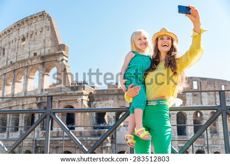 A brunette mother wearing a hat in the summer in Rome is holding her blonde daughter. They are smiling and taking a selfie. In the distance, the Colosseum. - stock photo