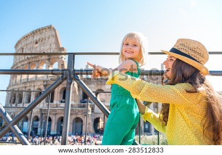 A brunette mother wearing a hat in the summer in Rome is sitting next to her blonde, smiling daughter, and pointing. They are happy. In the distance, the Colosseum and crowds of summer tourists. - stock photo