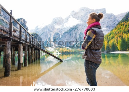 A brunette wearing outdoor gear stands smiling, looking at a wooden pier. The trees, mountains, and fall colours are reflecting in the water. A wooden pier, house, and bridge add rustic charm. - stock photo