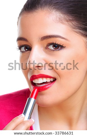 A brunette woman applying red lipstick - stock photo