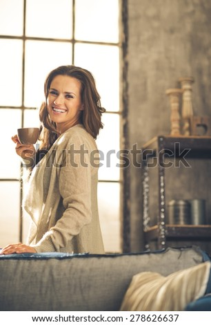 A brunette woman in comfortable clothing is smiling over her shoulder, holding up a hot cup of coffee. Industrial chic background, and cozy atmosphere. Loft decoration details. Upper body shot. - stock photo