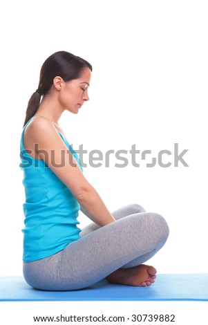 A brunette woman sat in a relaxed position on a yoga mat, isolated on a white background. - stock photo