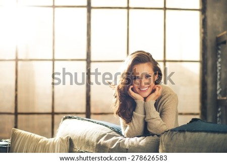A brunette woman with long brown hair leans over a sofa, smiling, resting her chin in her hands. The loft living room background has a  chic urban vibe. - stock photo
