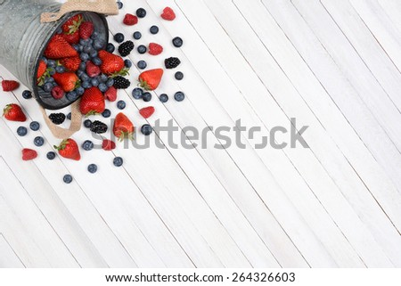 A bucket of berries spilling onto a rustic white kitchen table. High angle shot with the pail in the upper left corner leaving room for your copy. - stock photo